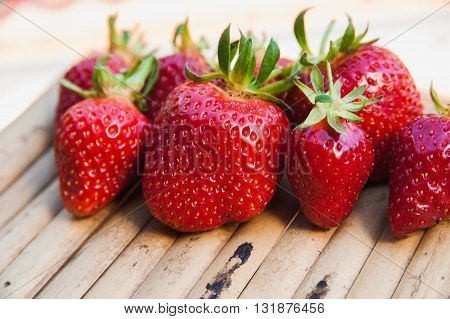 a Berries juicy strawberries on a wooden background