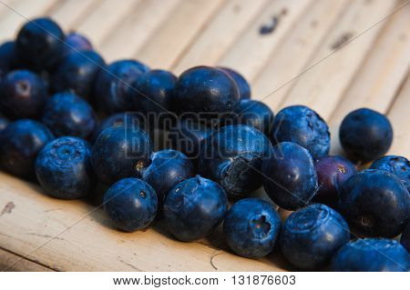 a Berries are juicy blueberries on a bamboo surface