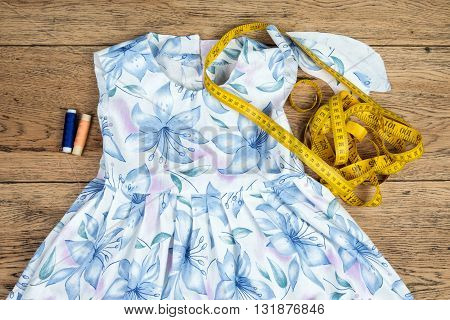 Still life of thread tape measures and elements cotton dress lying on the old vintage wooden table