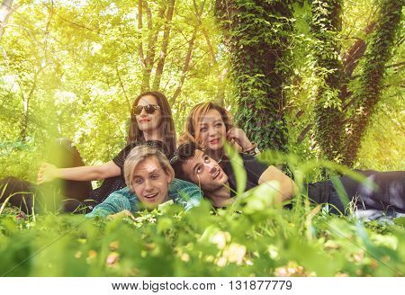 Group of young friends sitting on grass and relaxing