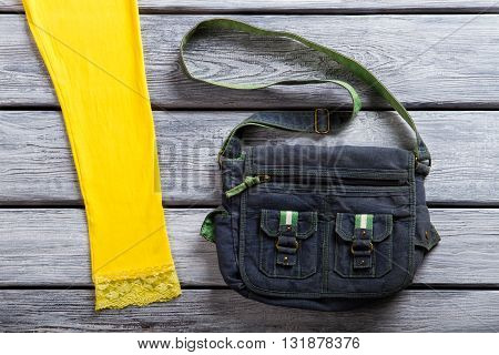 Denim bag of navy color. Handbag on gray wooden background. Girl's casual purse on display. Practical and simple.