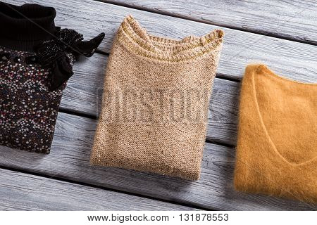 Different color sweatshirts. Folded sweaters on wooden background.