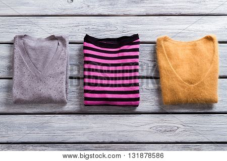 Pink and black striped pullover. Sweaters on gray wooden background. What to wear this autumn.