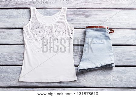 White tank top and shorts. Light blue shorts with belt.