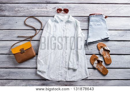 White shirt and blue shorts. Casual shirt and flip flops. New sunglasses on boutique showcase. Attractive summer outfit.