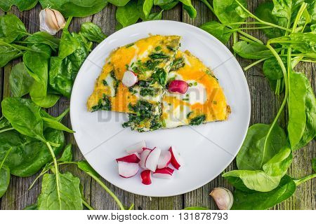 Top View on a Spinach Omelette with Radish and Garlic on a White Plate on Old Wooden Table
