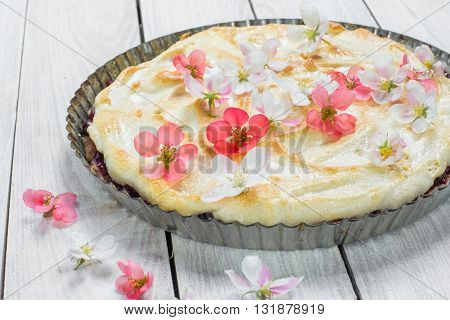 Fruit Pie with Flowers and Whipped Egg Whites on a Wood Table
