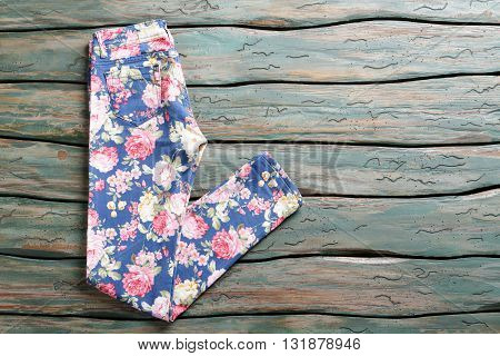 Blue trousers with floral print. Folded casual pants. Girl's trousers on green shelf. Item sold at auction.