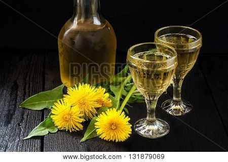 Cooled homemade dandelion wine in old wineglasses bottle and wreath from dandelions on a dark background
