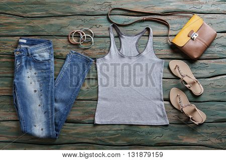 Gray top and blue jeans. Denim pants and brown bag. Lady's leather purse on shelf. New designer clothes and accessories.