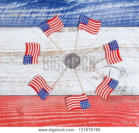 Small USA flags forming circle around American liberty dollar coin on red white and blue rustic boards. Fourth of July holiday concept for United States of America.