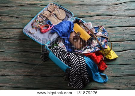 Opened suitcase with crumpled clothes. Sandals and bracelets in luggage bag. Don't break the sunglasses. Ready to travel.