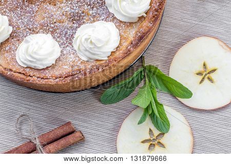 Top View on Apple Pie with Whipped Cream with Cinnamon Mint and Apple Slices on White Table