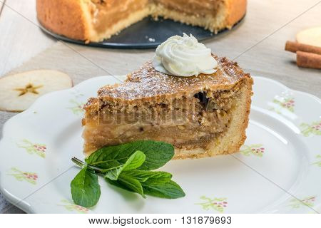 One Slice Apple Pie with Whipped Cream and Mint on a Plate on White Table