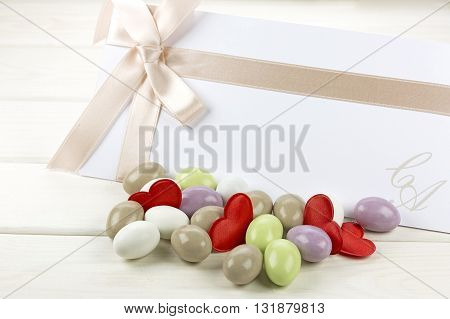 Colored sugared almonds red heart shaped confetti and wedding paper on white wooden background