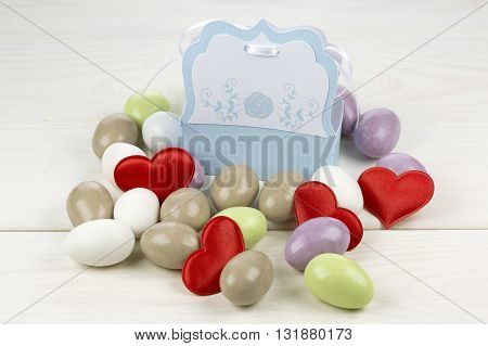 Colored sugared almonds red heart shaped confetti and papery box on white wooden background