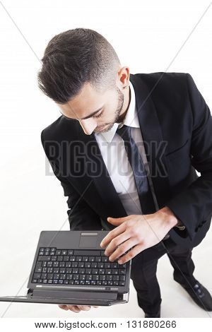 Portrait Of Young Businessman With Laptop Isolated On White Background