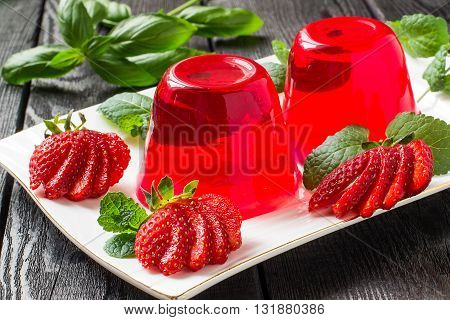 Tasty strawberry jelly and ripe strawberries on plate on a dark wooden table