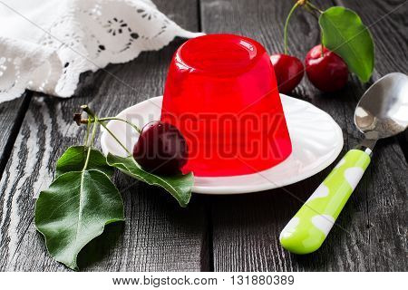 Delicious cherry jelly and ripe cherries with leaves on a dark wooden table. Selective focus