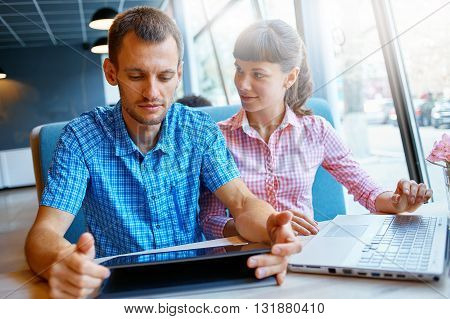young man and woman with laptop typing on the keyboard in cafe.