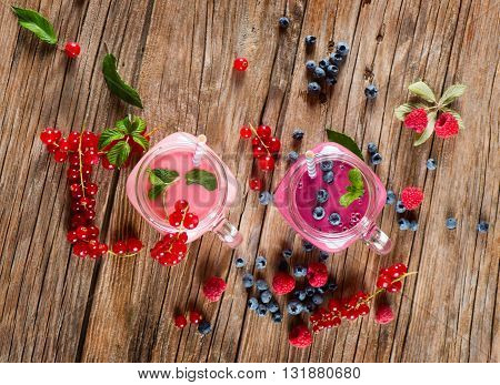 Top view of smoothie of berry (red currant blueberry raspberry) in a mason jar and fresh berries on a rustic wooden background.