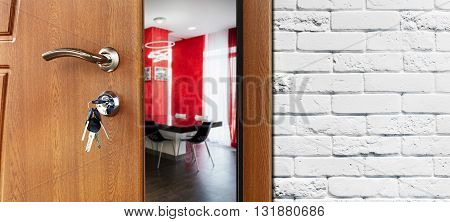 Half opened door to a kitchen. Door handle, door lock. Dining room door half open. Opening door. Welcome concept. Entrance to the room. Door at white brick wall, modern interior design.