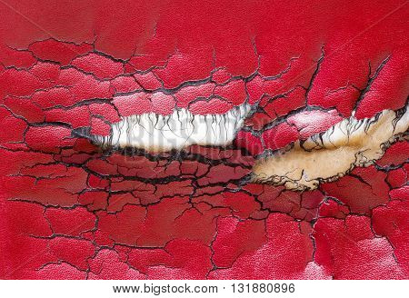 hole and cracks in the red leather sofa