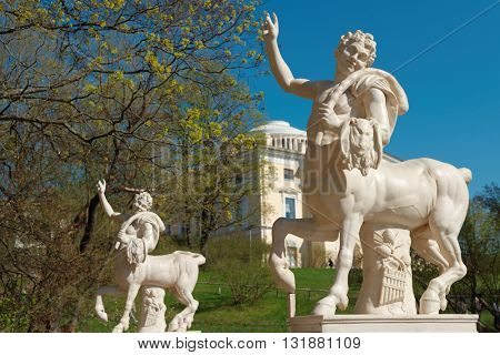 PAVLOVSK, ST. PETERSBURG, RUSSIA - MAY 8, 2016: Statues of centaurs at the Centaur bridge against Pavlovsk palace. The bridge was built in 1795-1797 by design of Vincenzo Brenna