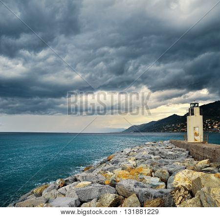 Lighthouse with thunderclouds and big sea stones
