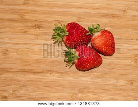 close up of big fresh strawberry on wood
