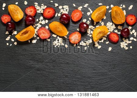 Concept of diet and healthy eating. Oat cereal with strawberries apricots and cherries in border on slate blackboard with space for text. Top view