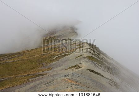 Path following a mountain ridge disapears in fog. Scene on Mt Robert New Zealand.