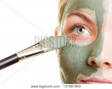 Skin care. Woman applying with brush clay mud mask to her face isolated. Girl taking care of dry complexion. Beauty treatment.
