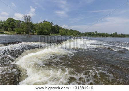 Waterfalls across a river in spring with blue skies