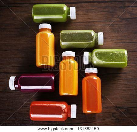 Detox drink in bottles on wooden background