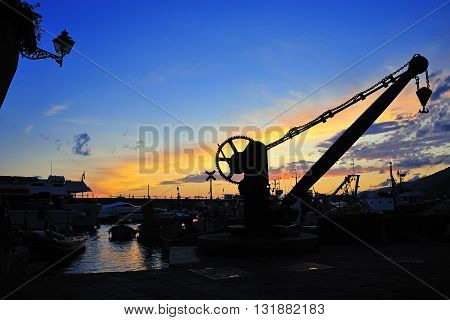 syluet of lift crane in the port at sunset in Camogli