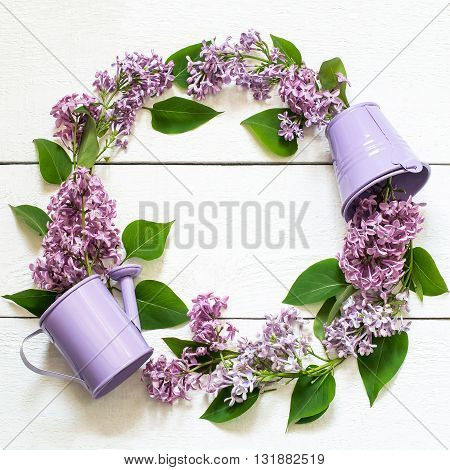 Colorful wreath of lilac with a decorative watering can and a bucket. Use for floral backgrounds holiday greetings and invitations postcard. Top view square image space for text