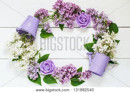 Colorful wreath of lilac with decorative watering can bucket and candles . Use for floral backgrounds holiday greetings and invitations postcards. Top view space for text
