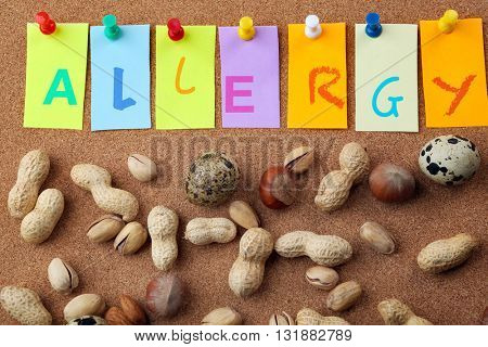 Word ALLERGY with nuts on cork board