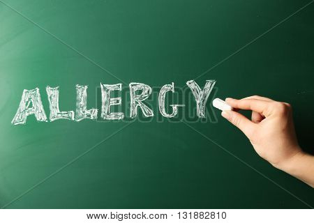Allergy food concept. Hand with chalk writing on blackboard