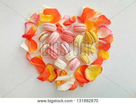 Fresh macaroons and rose petals, top view