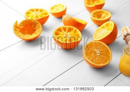 Juicing delicious oranges on white wooden table