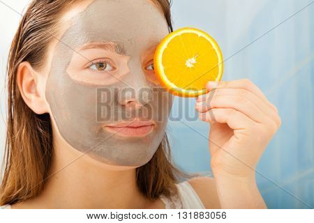 Woman With Mud Facial Mask Holds Orange Slice