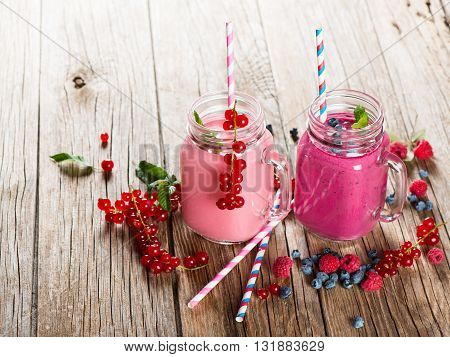 Smoothie of berry (red currant blueberry raspberry) in a mason jar and fresh berries on a rustic wooden background.