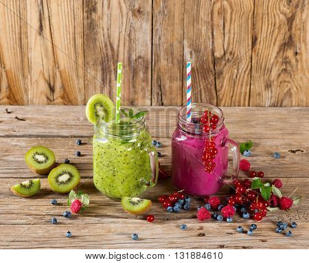Smoothie of berry and fruit (kiwi red currant blueberry raspberry) in a mason jar and fresh berries on a rustic wooden background with copy space.