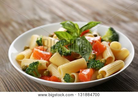 Plate of pasta with salmon and broccoli on table closeup