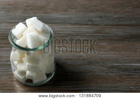 Glass jar with lump sugar on wooden table