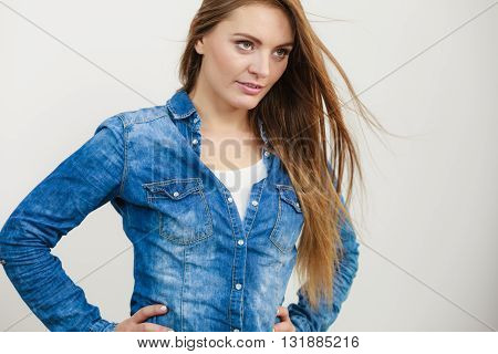Female fashion. Fashionable young attractive woman wearing denim jeans shirt. Girl with brown long hair waving on air.