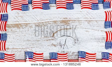 Small USA flags forming complete border on red white and blue rustic boards. Fourth of July holiday concept for United States of America.