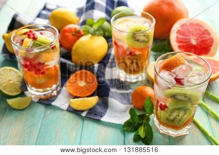 Refreshing cocktails with ice, mint, pomegranate seeds and slices of fruits on blue wooden background